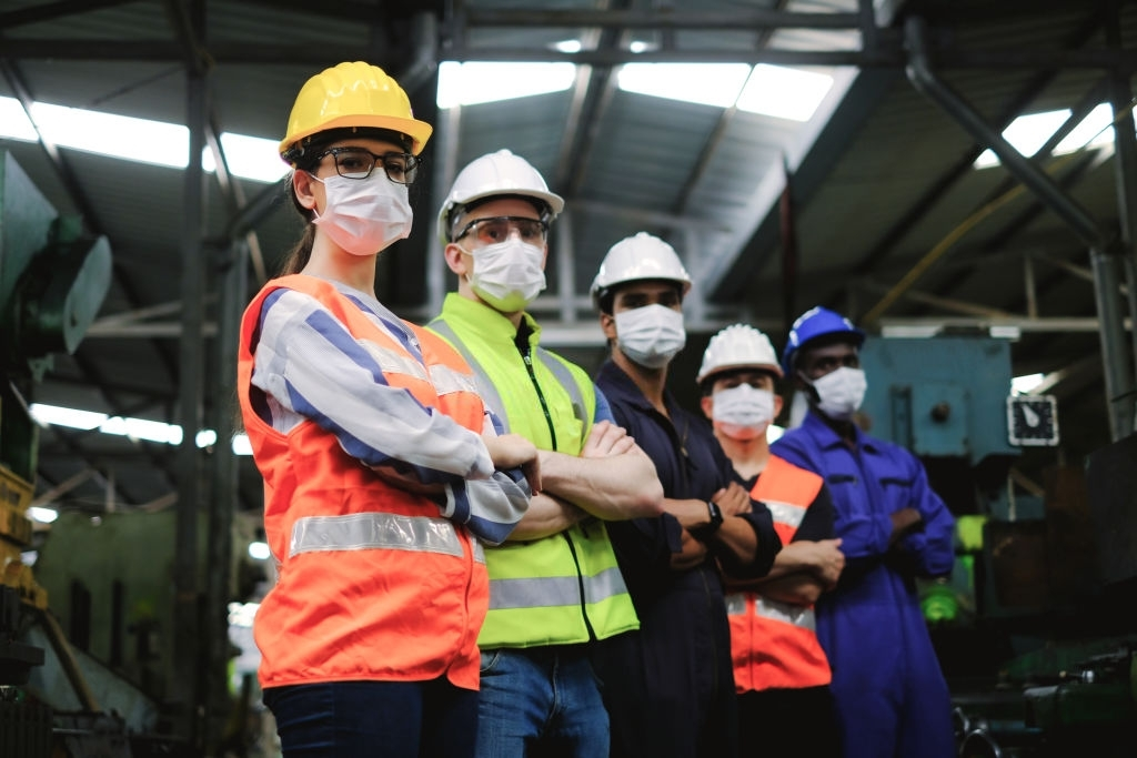 Industrial woman engineer wearing  hygiene face mask and hardhat with workers in factory,new normal of industry for protection covid-19 pandemic.